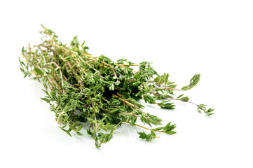 Green thyme herb branches on white wooden table background
