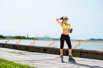 Young, beautiful, sporty and fit girl rollerblading on inline skates.