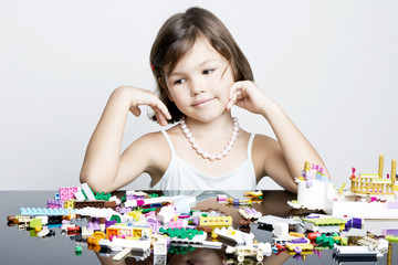 Little girl playing in lego blocks