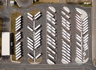 Aerial view to parking lot for autobus and trucks. Industrial background on transportation theme.