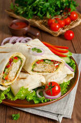 Shawarma with meat and vegetables wrapped in pita bread