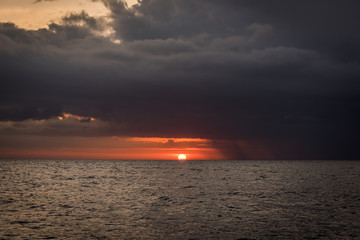 Sun setting between sea and black stormclouds