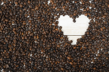 Top view of coffee beans in heart shape on wooden surface