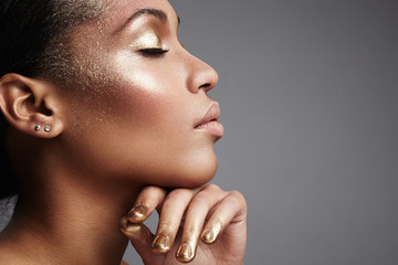 black woman's profile with a golden makeup