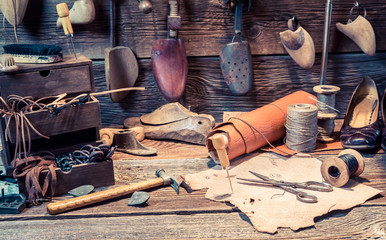 Vintage cobbler workplace with tools, leather and shoes