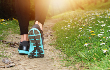 Woman running in nature, closeup on shoe. Sport, fitness jogging, active lifestyle concept