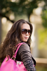 Beautiful latinonos woman wearing sunglasses, casual wear and handbag walking on the park. Fashionable girl in sunglasses and with a bag in her hand looking to the frame