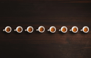 Set of small ceramic cups with espresso or ristretto, freshly brewed in artisan cafe, isolated in row line on wooden rich textured table, top view