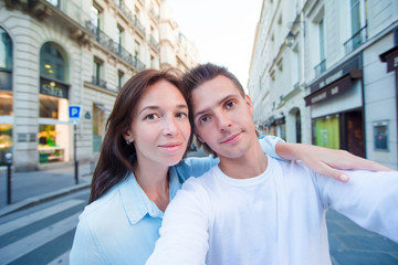 Happy young couple taking selfie in Paris outdoors