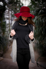 beautiful young brown-haired woman with long hair, beautiful makeup with bright red lips, wearing a gray coat, black pants, a scarf, a hat and sunglasses walking in a greenhouse