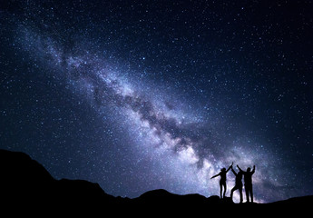 Landscape with blue Milky Way. Night starry sky with silhouette of a happy family with raised-up arms on the mountain. Beautiful Universe. Space background