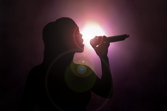 Women singing under spotlight