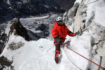 Khumbu, Nepal - Dec 17, 2013: Unidentified rock climber in fully Everest down suit on Icecovered rock face of Mount Ama Dablam, Khumbu Nepal