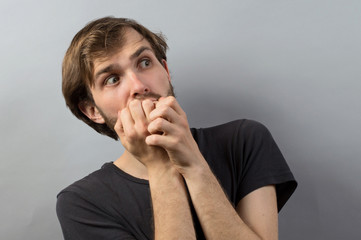 young business man biting his nails. on a light gray studio background