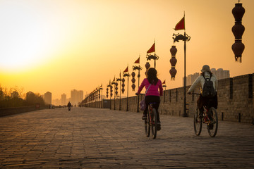 Stores à enrouleur Xian XIAN, CHINA - MARCH 13 2016: People ride bicycle on City Wall of Xi'an famous Historic Sites in china sunset in the evening