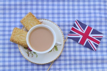 Traditional milky tea served in a bone china cup and saucer with custard cream type biscuits with a Union Jack flag