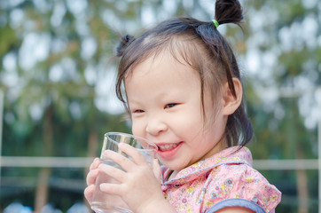Little Asian girl smiles after drinking water from glass