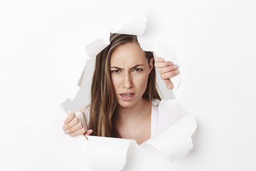 Angry young woman looking through torn paper, portrait