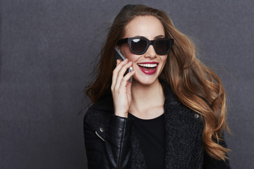 Lady laughing on phone in sunglasses