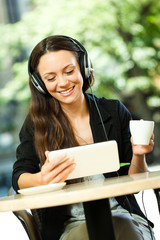 Young woman is using tablet and listening music in cafe.