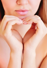 Pretty girl making a heart symbol with her hands