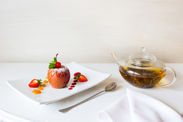 Vegetatian's desert. Baked apple with a fruit jam on a square white plate and a pot of herbal tea