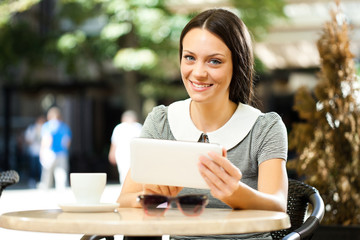 Young woman is using digital tablet in a cafe.