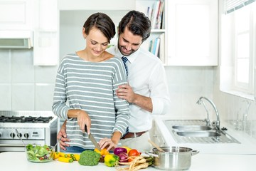 Couple chopping vegetables at table in kitchen