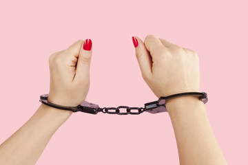 Female hands with red nails in handcuffs.