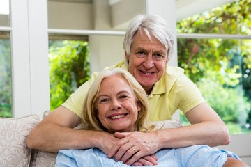 Happy senior couple sitting in living room at home