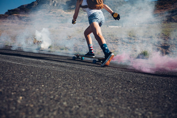 Young woman skateboarding on a road