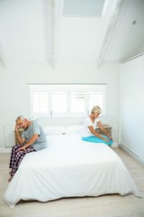 Senior man and woman sitting on bed