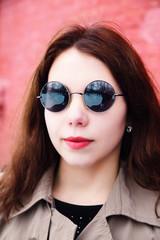 Brunette long hair girl in sunglasses walking outdoor