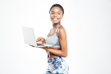 Cheerful beautiful young african american sportswoman standing and using laptop