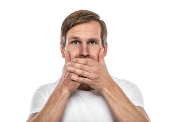 Man covering mouth with hands and looking at camera.