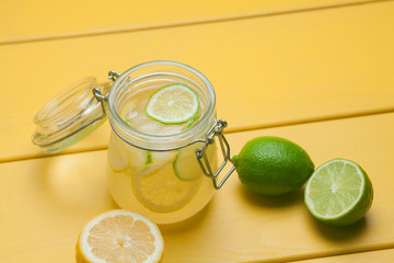 Lemonade with ice, lemon and lime in a jar on a yellow wooden ba
