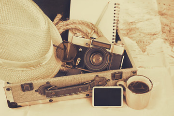 traveling concept. camera, cup of coffee, sunglasses, fedora hat and notebook. sepia vintage style filtered. selective focus