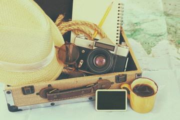 traveling concept. camera, cup of coffee, sunglasses, fedora hat and notebook. vintage filtered. selective focus