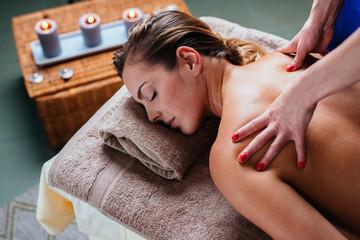 Beautiful woman getting thai massage in exotic spa