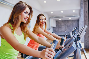 Happy women doing cardio workout on bike at gym