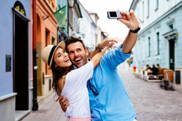 Happy couple taking selfie on the street during vacation in Euro Fototapete