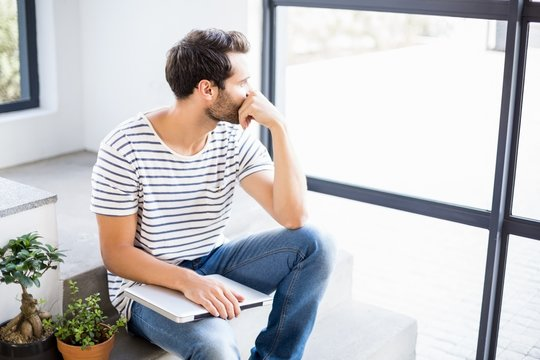 Man sitting with laptop looking out through window