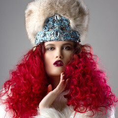 Incredibly beautiful fashion image of  girl with red hair. Dressed in a white fur coat and fur hat. Strong emotions and passion. Gray background