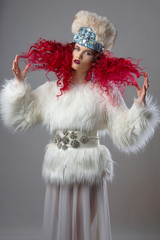 Incredibly beautiful fashion image of  girl with red hair. Dressed in a white fur coat and fur hat. Girl throws up his curly hair. Gray background