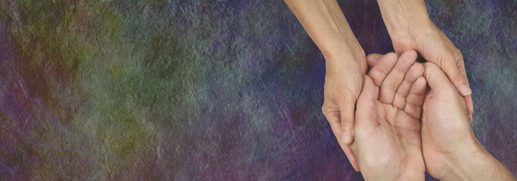 Caring for those in need -  rustic dark stone effect wide background with a womans hands cupped around a mans hands depicting a carer