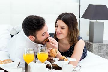 Honeymoon couple having breakfast in hotel room.