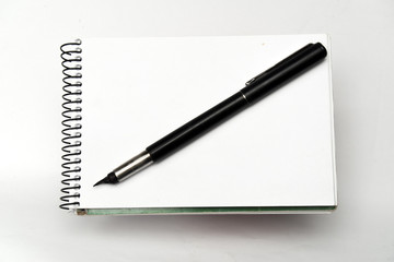 black pen on notebook on white background