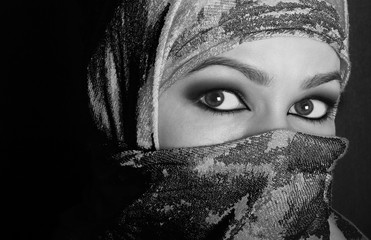 close-up beautiful mysterious eyes eastern woman wearing a hijab. black and white