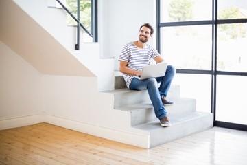 Happy man sitting on steps using laptop