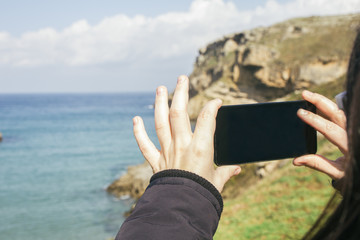 Woman taking a photo with her phone of the sea